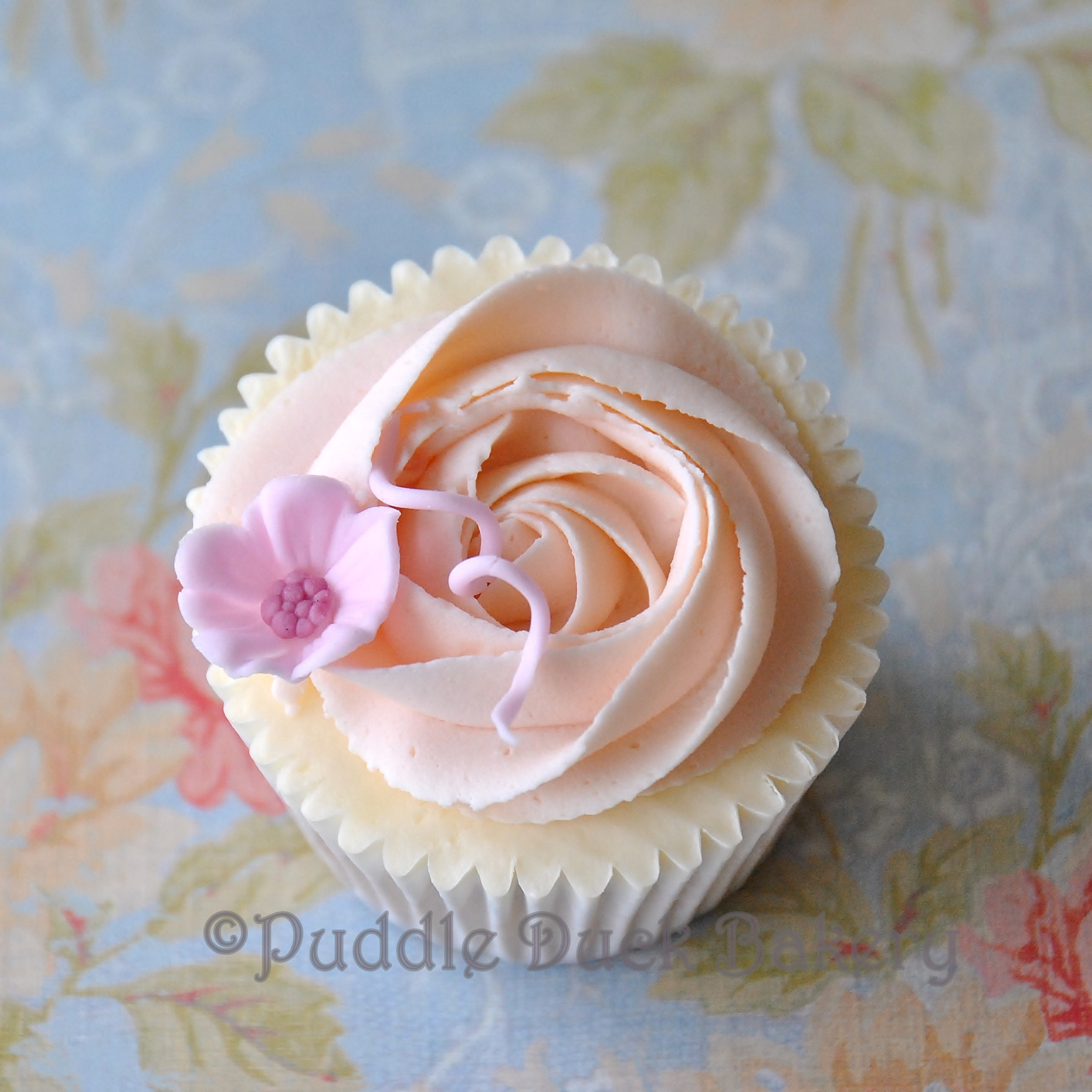 A swirl and a small flower on a cupcake