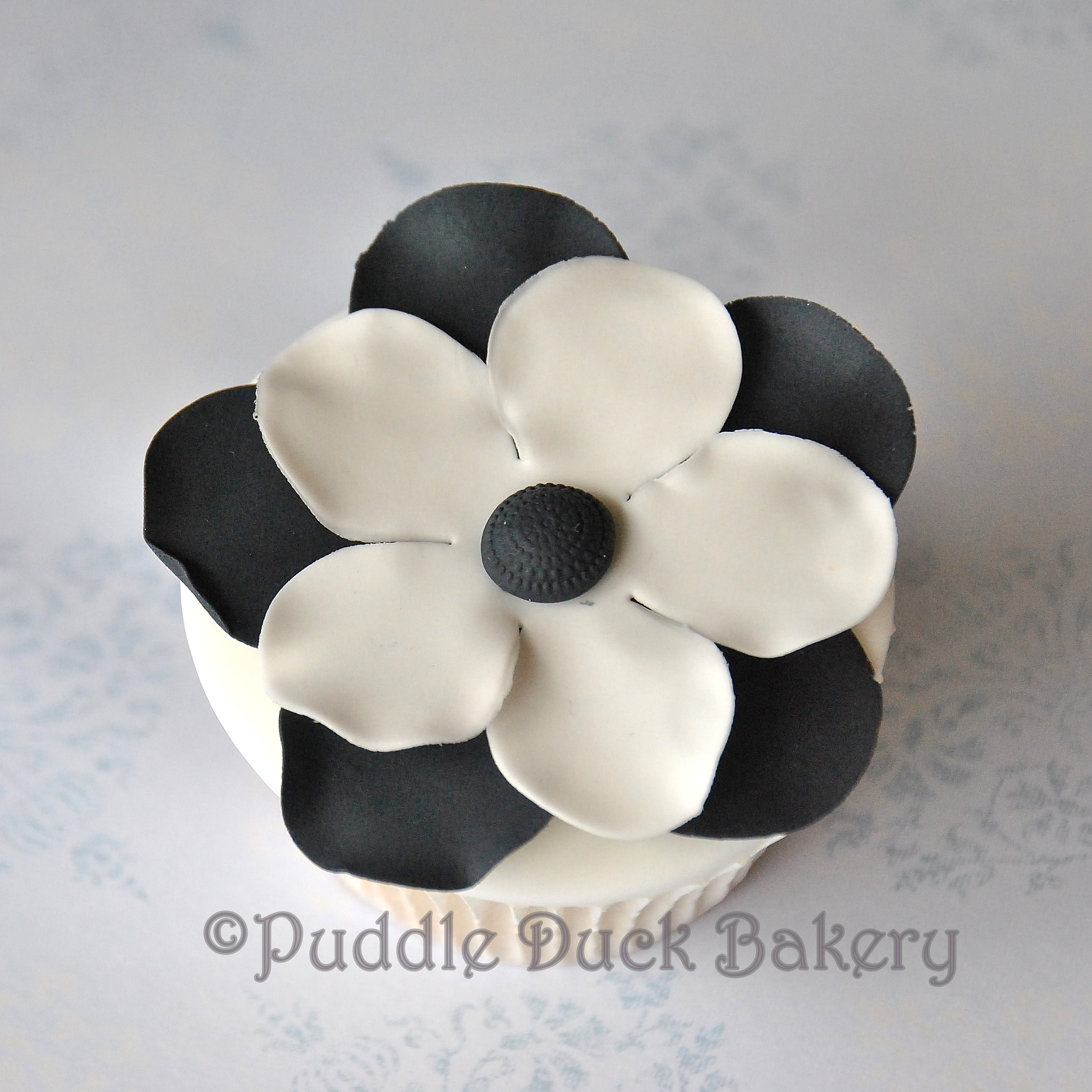 A black and white flower on a cupcake