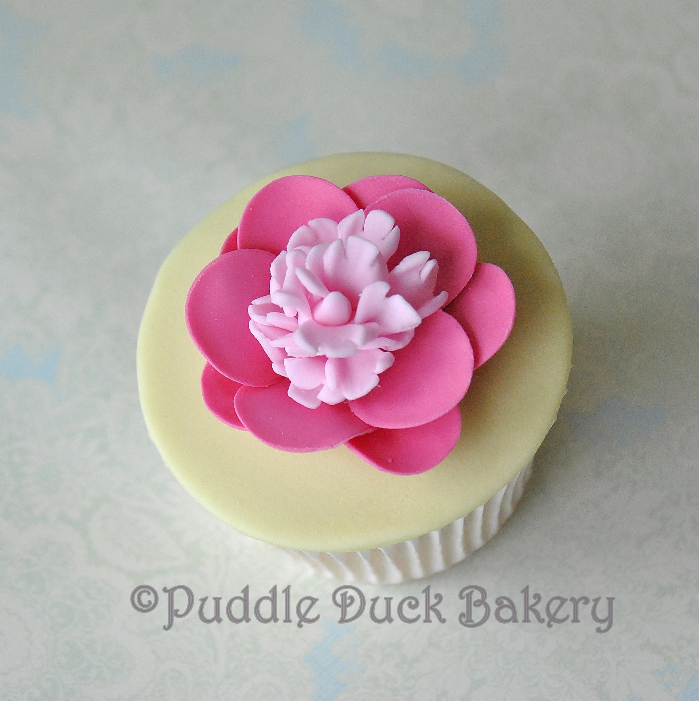 A pink flower on a cupcake