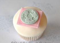 Using a stamp to decorate a button on a cupcake